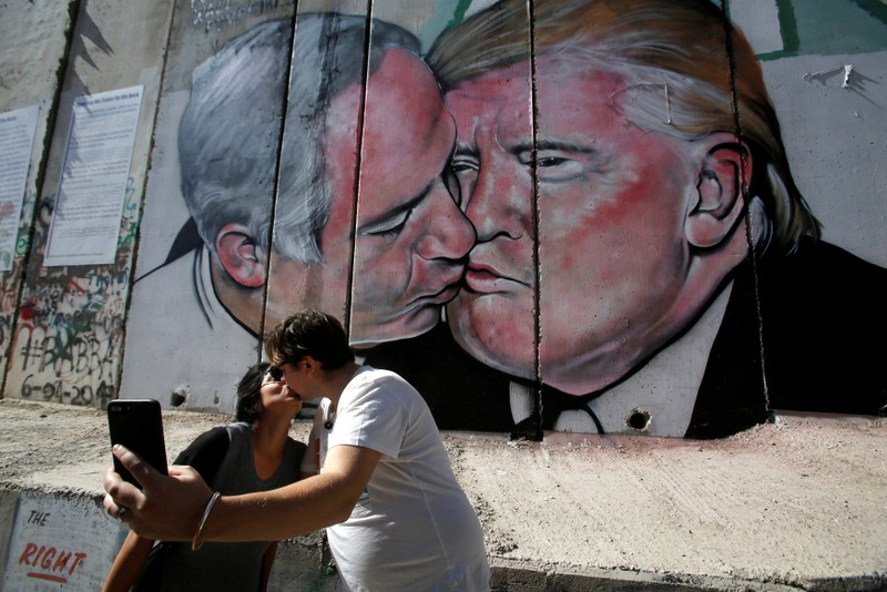 Tourists kiss each other as they stand in front of a mural depicting U.S. President Donald Trump and Israel's Prime Minister Benjamin Netanyahu kissing each other in the West Bank city of Bethlehem