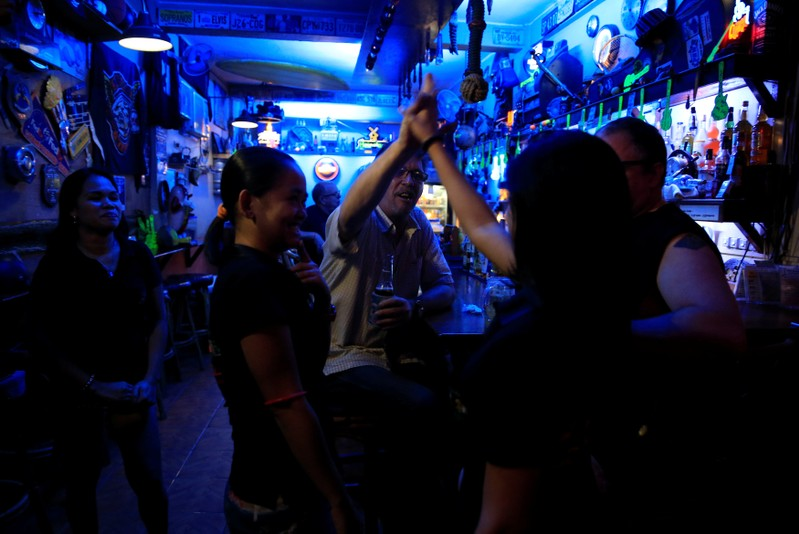 American James John Goodman, 51, does a high-five with female servers inside a bar in Subic, north of Manila