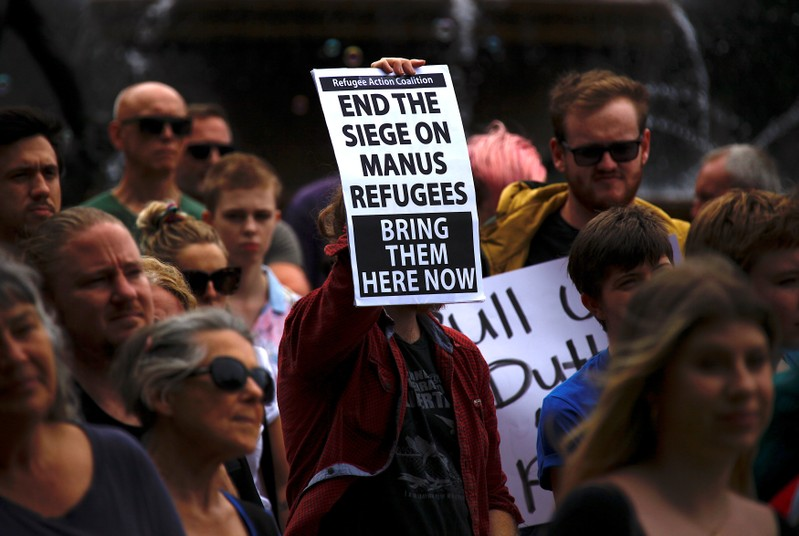 Refugee advocates hold placards as they participate in a protest in Sydney, Australia, against the treatment of asylum-seekers at Australia-run detention centres located at Nauru and Manus Island