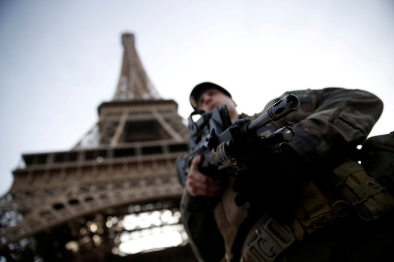 FILE PHOTO: French soldier stands guard under the Eiffel Tower in Paris