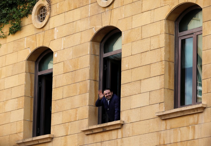 Saad al-Hariri who suspended his decision to resign as prime minister gestures to his supporters at his home in Beirut