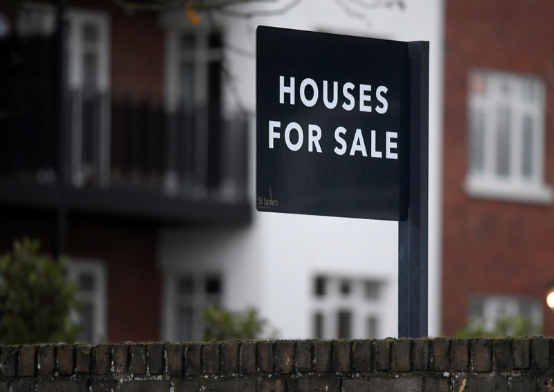 Property sale signs are seen outside of a group of newly built houses in west London