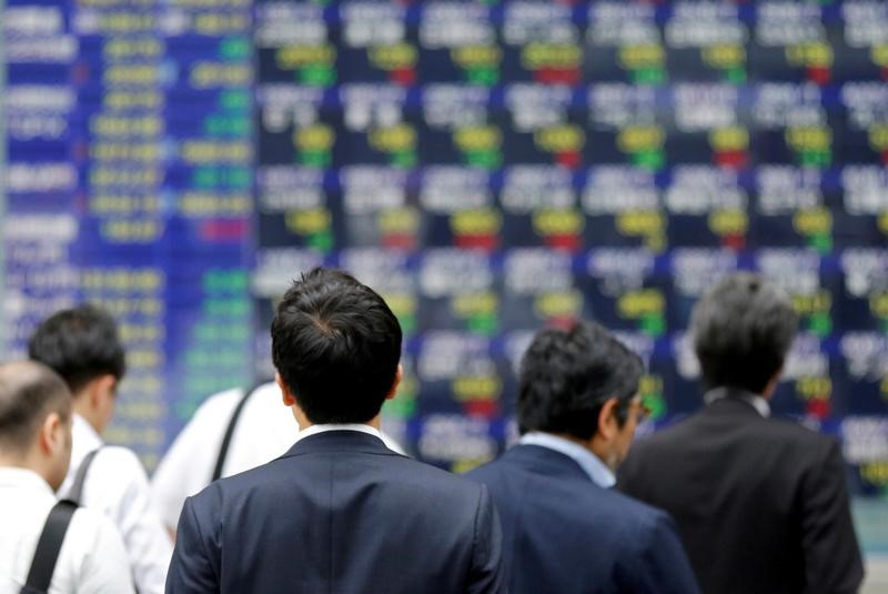 FILE PHOTO: People walk past an electronic stock quotation board outside a brokerage in Tokyo