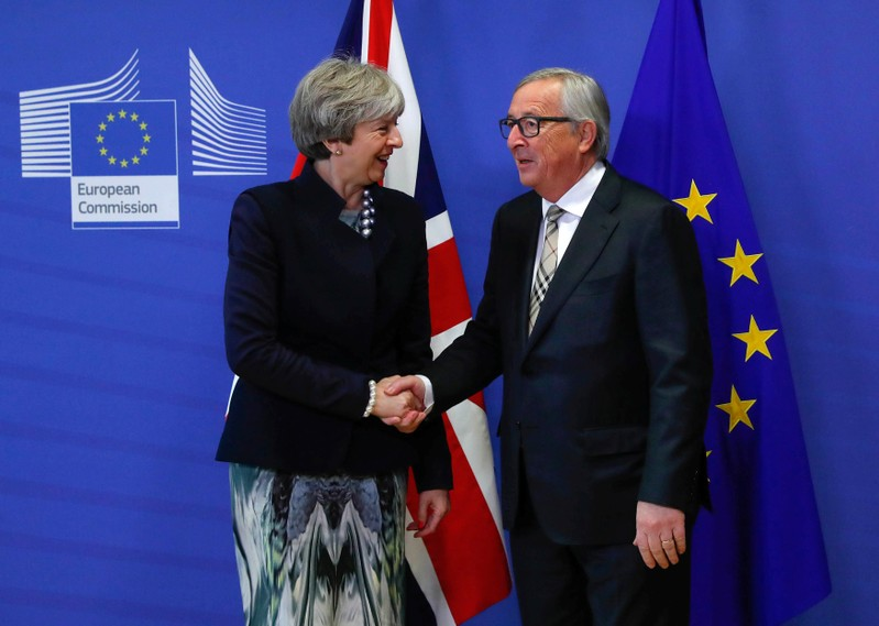 FILE PHOTO - Britain's Prime Minister Theresa May is welcomed by European Commission President Jean-Claude Juncker at the EC headquarters in Brussels