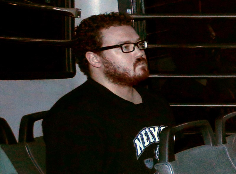 FILE PHOTO: Jutting, a British banker charged with two counts of murder, sits in the back row of a prison bus as he arrives at the Eastern Law Courts in Hong Kong