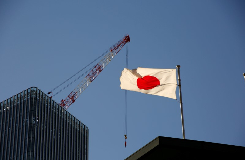 Japan's national flag is seen in front of a crane at a construction site at a business district in Tokyo