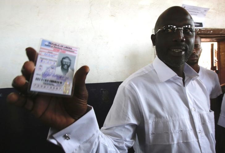 Weah, former soccer player and presidential candidate of CDC shows his voter's card in Monrovia