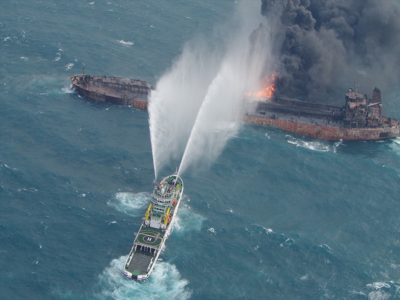 A rescue ship works to extinguish the fire on the stricken Iranian oil tanker Sanchi in the East China Sea