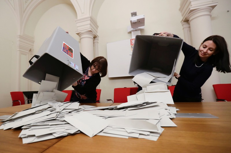 Election committee members are seen as they count votes after polling stations closed for the country's direct presidential election in Prague