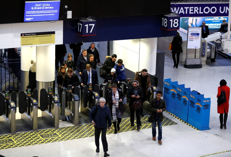 On the day that rail fares increase, passengers arrive at Waterloo Station in London