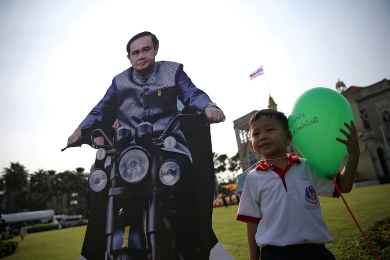 A boy poses next to a cardboard cut-out of Thailand's Prime Minister Prayuth Chan-ocha during preparations for national Children's Day at Government House in Bangkok