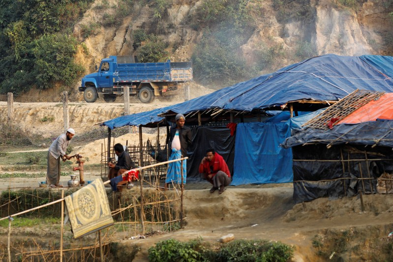A Burmese vehicle drives behind Rohingya refugee camp at no man's land between Bangladesh-Myanmar border, in Cox's Bazar