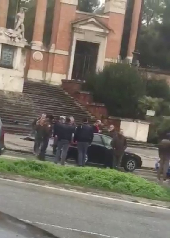 People gather where witnesses say a shooter was arrested in Macerata