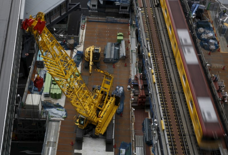 Heavy machineries are seen next to a subway train at a construction site in Tokyo