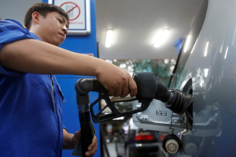 FILE PHOTO: An employee pumps petrol into a car at a petrol station in Hanoi