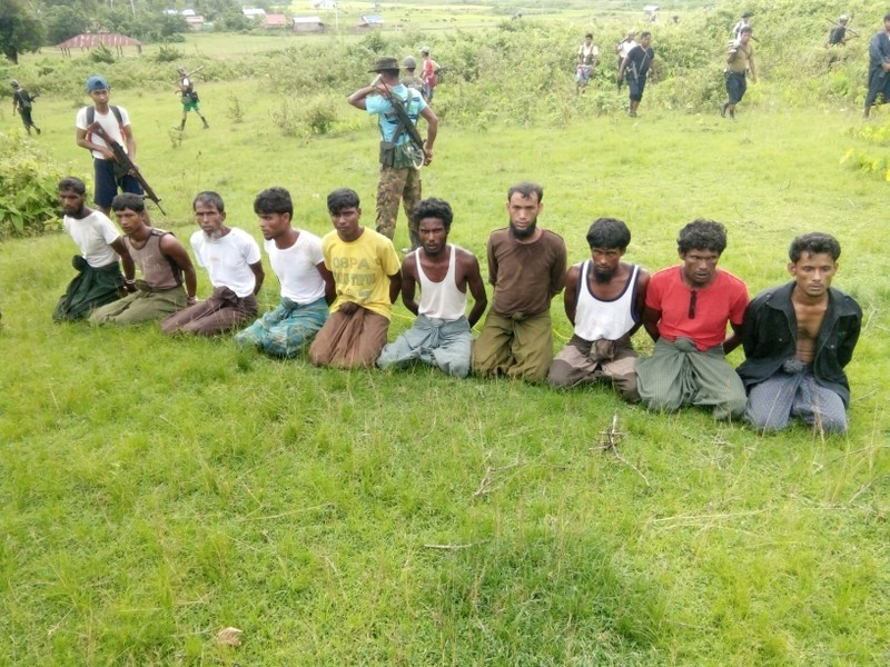 Ten Rohingya Muslim men with their hands bound kneel as members of the Myanmar security forces stand guard in Inn Din village