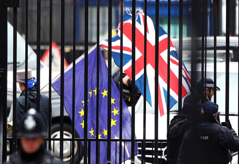 FILE PHOTO: A demonstrator carries a Union Jack and a European Union flag as the EU's chief Brexit negotiator Michel Barnier visits Downing Street in London
