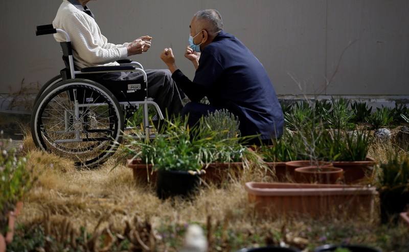 A 92-year-old man in a wheel chair, imprisoned for life in the Tokushima prison, for murder, rape and other offences, exercises with a care worker in a courtyard at the Tokushima prison in Tokushima