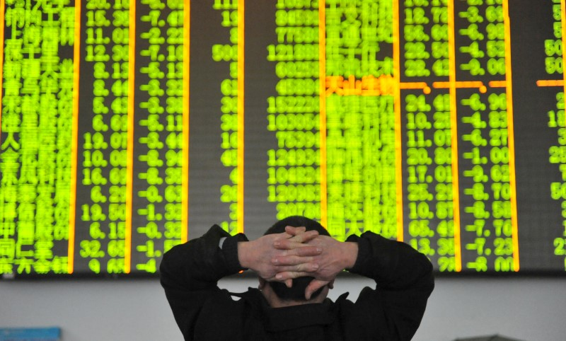FILE PHOTO: An investor looks at an electronic screen at a brokerage house in Hangzhou