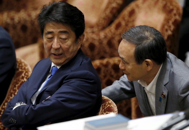 Japan's Prime Minister Abe talks with Chief Cabinet Secretary Suga at a lower house special committee session on security-related legislation at the parliament in Tokyo
