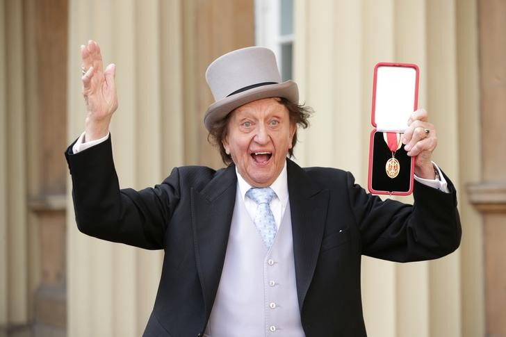 FILE PHOTO: Entertainer Ken Dodd poses for photographers after being made a Knight Bachelor of the British Empire by Britain's Prince William at an investiture at Buckingham Palace in central London