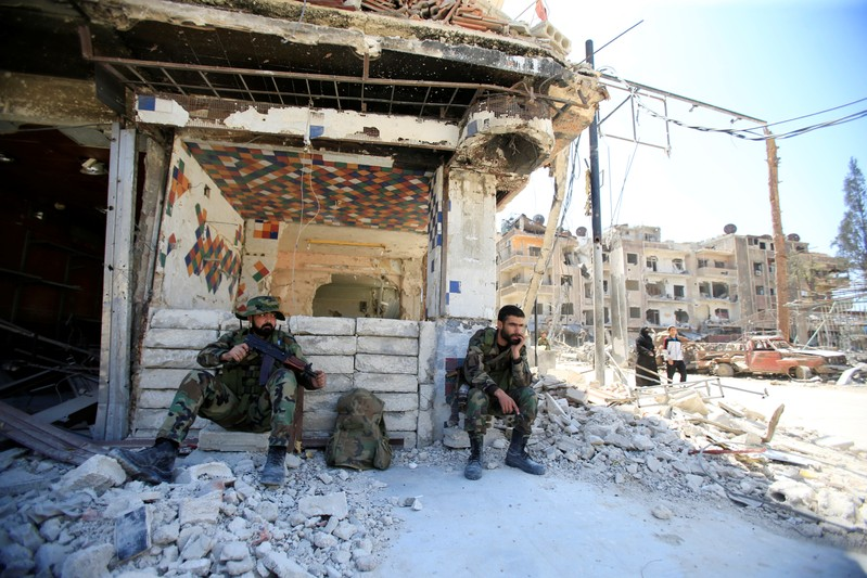 Members of Syrian police sit at a damaged building at the city of Douma, Damascus