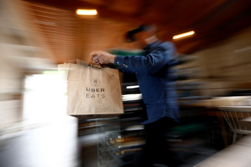 A bag of donuts destined for delivery via Uber Eats is rushed to a driver from a kitchen in Sydney