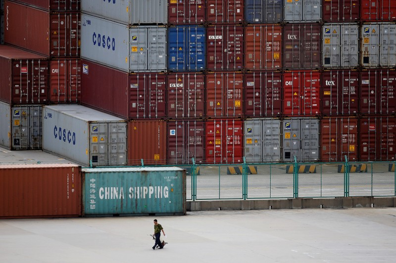 FILE PHOTO: A man walks past a container area at the Yangshan Deep Water Port, part of the newly announced Shanghai Free Trade Zone, south of Shanghai