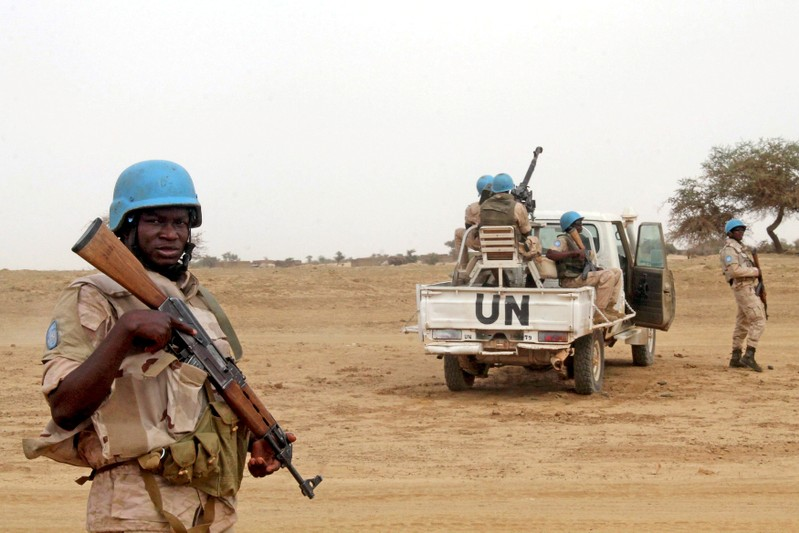 FILE PHOTO: FILE PHOTO: UN peacekeepers stand guard in the northern town of Kouroume