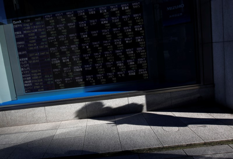A pedestrian casts a shadow in front of an electronic stock quotation board outside a brokerage in Tokyo, Japan