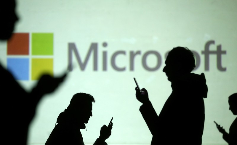 Silhouettes of mobile users are seen next to a screen projection of Microsoft logo in this picture illustration