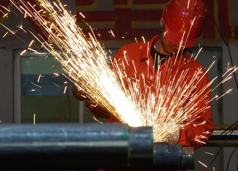 A worker polishes steel pipes at a factory of Dongbei Special Steel Group Co Ltd in Dalian