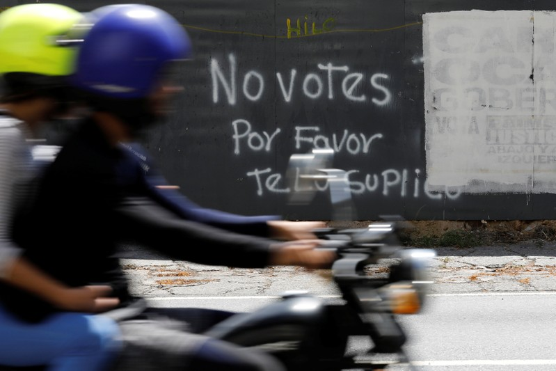 A motorcycle passes graffiti painted on a fence in Caracas