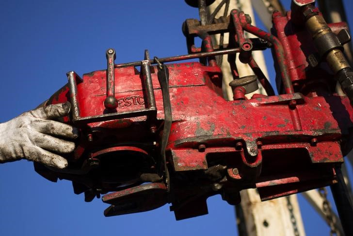 FILE PHOTO: A man works on the rig of an oil drilling pump site in McKenzie County outside of Williston