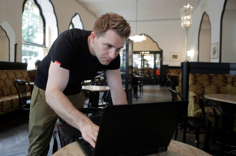 Austrian lawyer and privacy activist Schrems prepares his laptop during a Reuters interview in Vienna