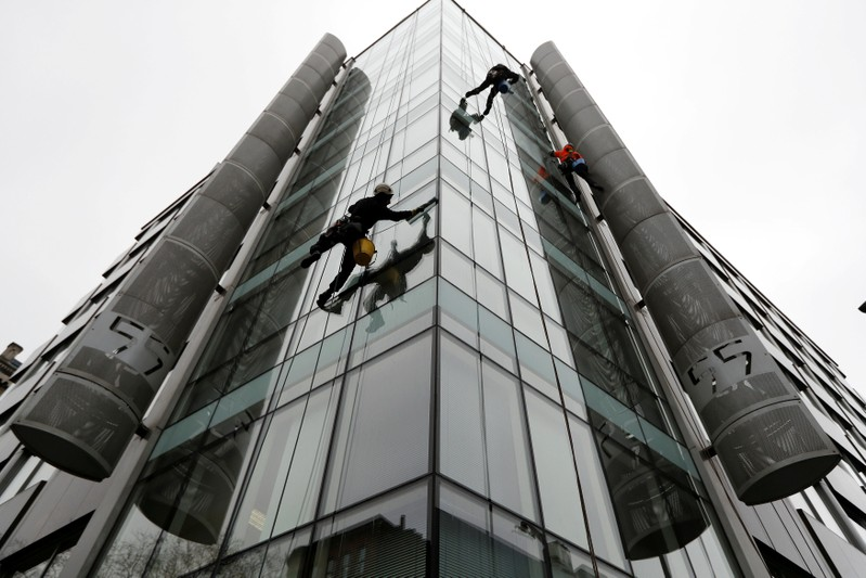 FILE PHOTO: Window cleaners work outside the offices of Cambridge Analytica in central London