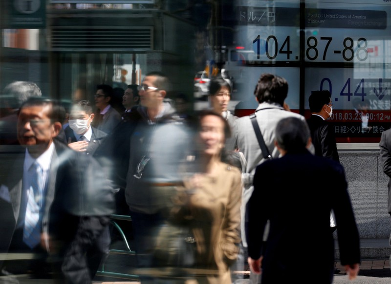 FILE PHOTO: People walk past an electronic board showing exchange rate between Japanese Yen and U.S. Dollar outside a brokerage at a business district in Tokyo