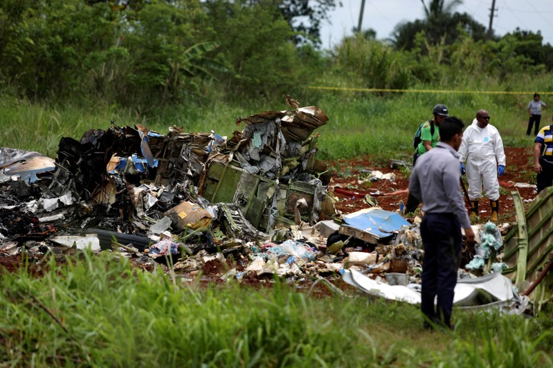 Rescue team members work on the wreckage of a Boeing 737 plane that crashed in the agricultural area of Boyeros