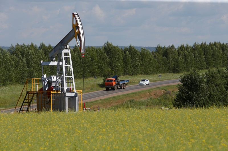 Cars drive past a pump jack at the Ashalchinskoye oil field owned by Russia's oil producer Tatneft near Almetyevsk, in the Republic of Tatarstan