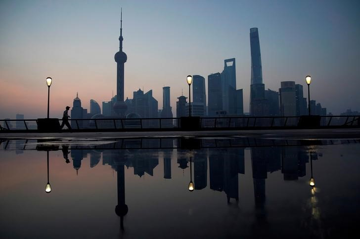 FILE PHOTO: A security guard walks on the bund in front of the financial district of Pudong in Shanghai