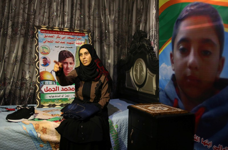 Mother of Palestinian Hiatham Al-Jamal, 15, who was killed during a protest at the Israel-Gaza border, gestures as she shows clothes he bought to wear during Eid al-Fitr holiday, in Rafah in the southern Gaza Strip
