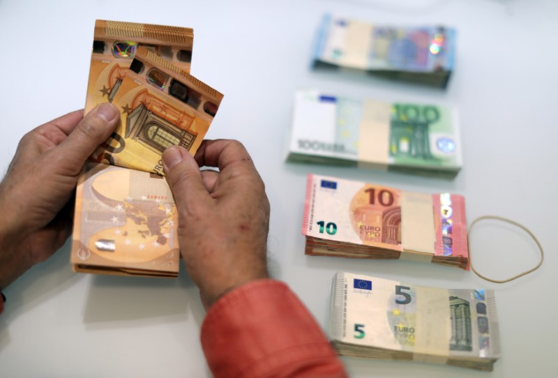 A money changer counts Euro banknotes at a currency exchange office in Nice