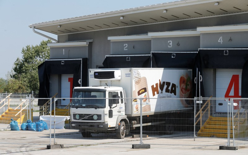 FILE PHOTO: A truck in which 71 dead migrants were found is parked at a customs building with refrigeration facilities in the village of Nickelsdorf