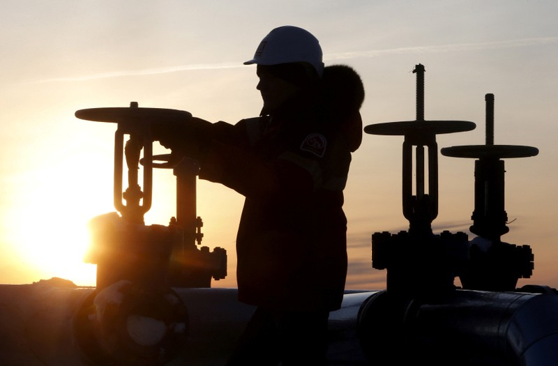 FILE PHOTO: Worker checks valve of oil pipe at Lukoil company owned Imilorskoye oil field outside West Siberian city of Kogalym