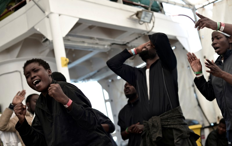 Migrants sing on the deck of MV Aquarius on their way to Spain