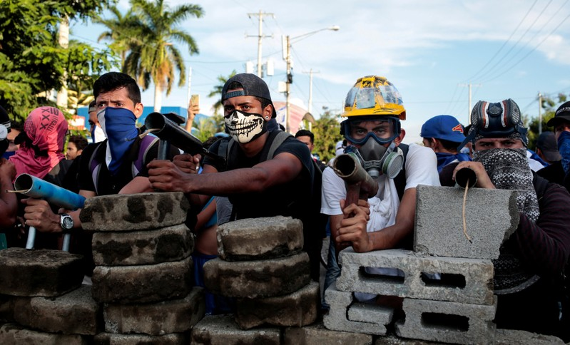 Demonstrators stand behind a barricade during clashes with riot police during a protest against Nicaragua's President Daniel Ortega's government in Managua