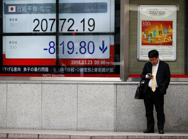 Man looks at a mobile phone next to an electronic board showing Japan's Nikkei average outside a brokerage in Tokyo