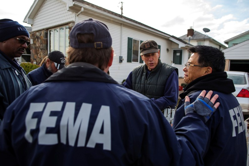 FILE PHOTO: Representatives from FEMA speak with resident of Staten Island borough neighborhood of New Dorp Beach about registering with the agency in New York