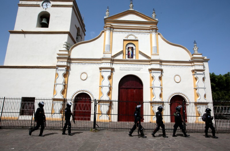 Members of Nicaragua's Special Forces walk past a church during clashes with anti-government protesters in the indigenous community of Monimbo in Masaya