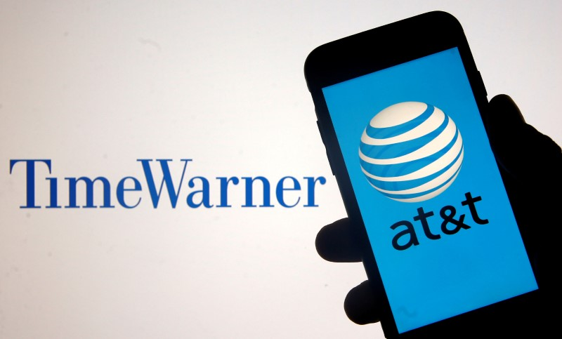 FILE PHOTO: Smartphone with AT&T logo is seen in front of displayed Time Warner logo in this picture illustration